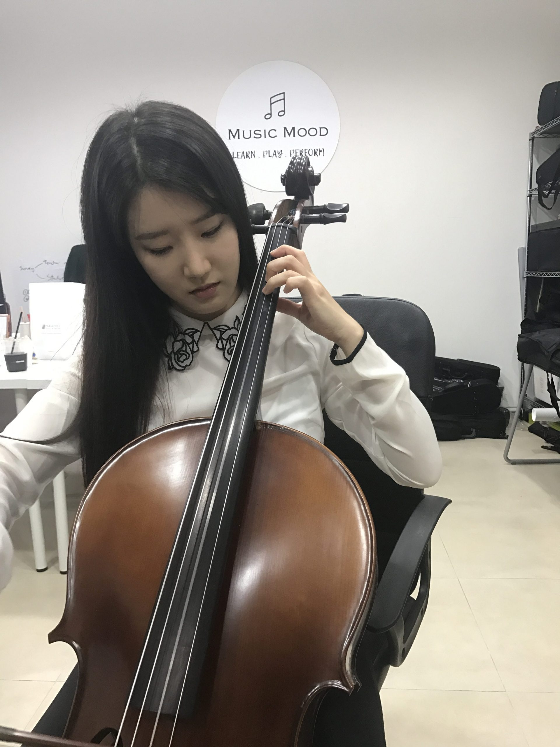 Sora trying out cello in singapore